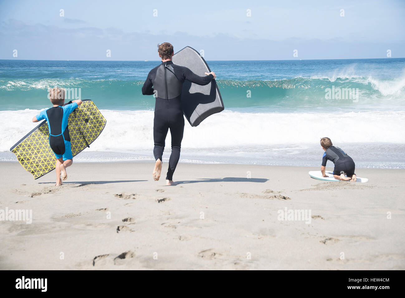 Rear view of father and two sons running with bodyboards on beach, Laguna Beach, California, USA Stock Photo