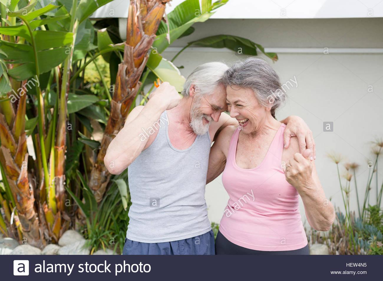 Youthful exercising senior couple laughing in garden - Stock Image