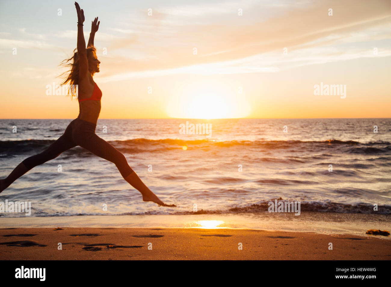 Woman leaping in mid air on beach at sunrise - Stock Image