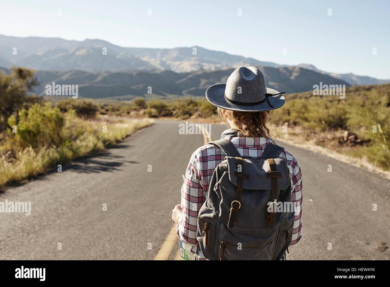Woman standing in desert road, looking ahead, Sedona, Arizona, USA - Stock Image