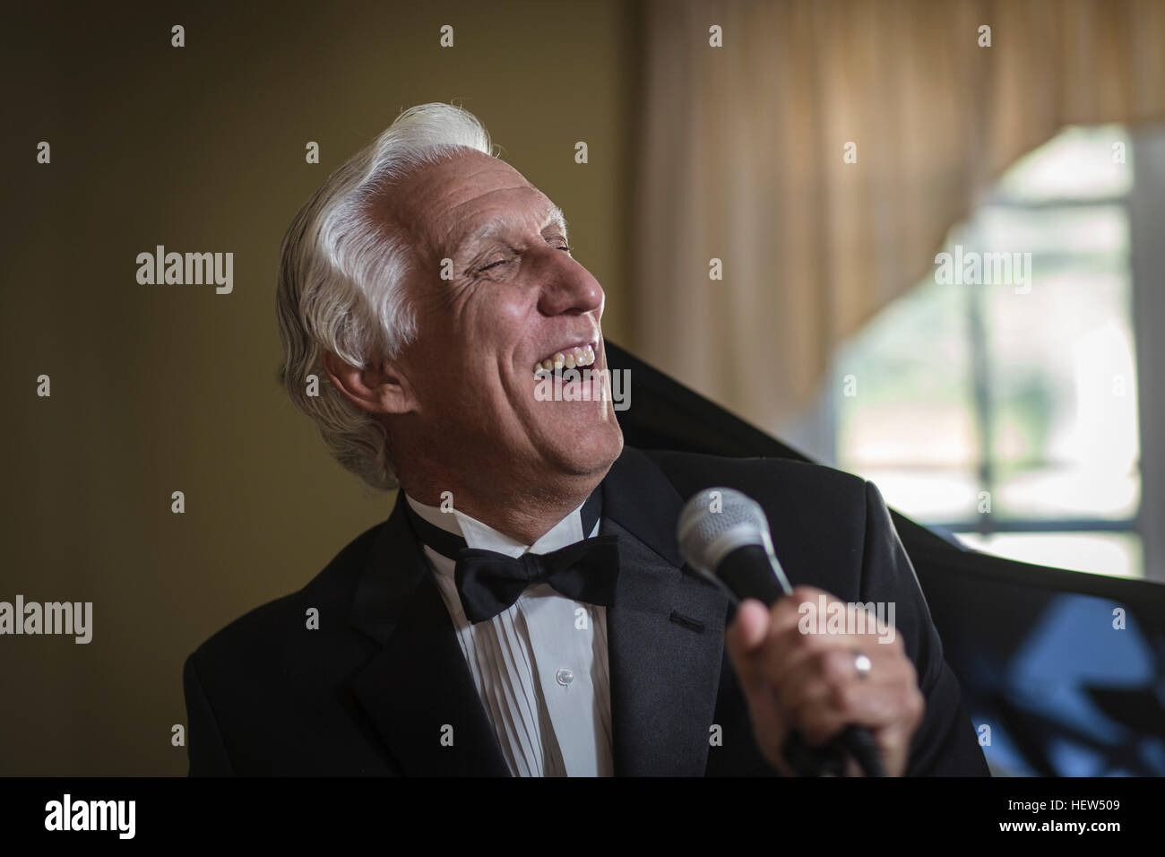 Senior man in bow tie singing into microphone - Stock Image