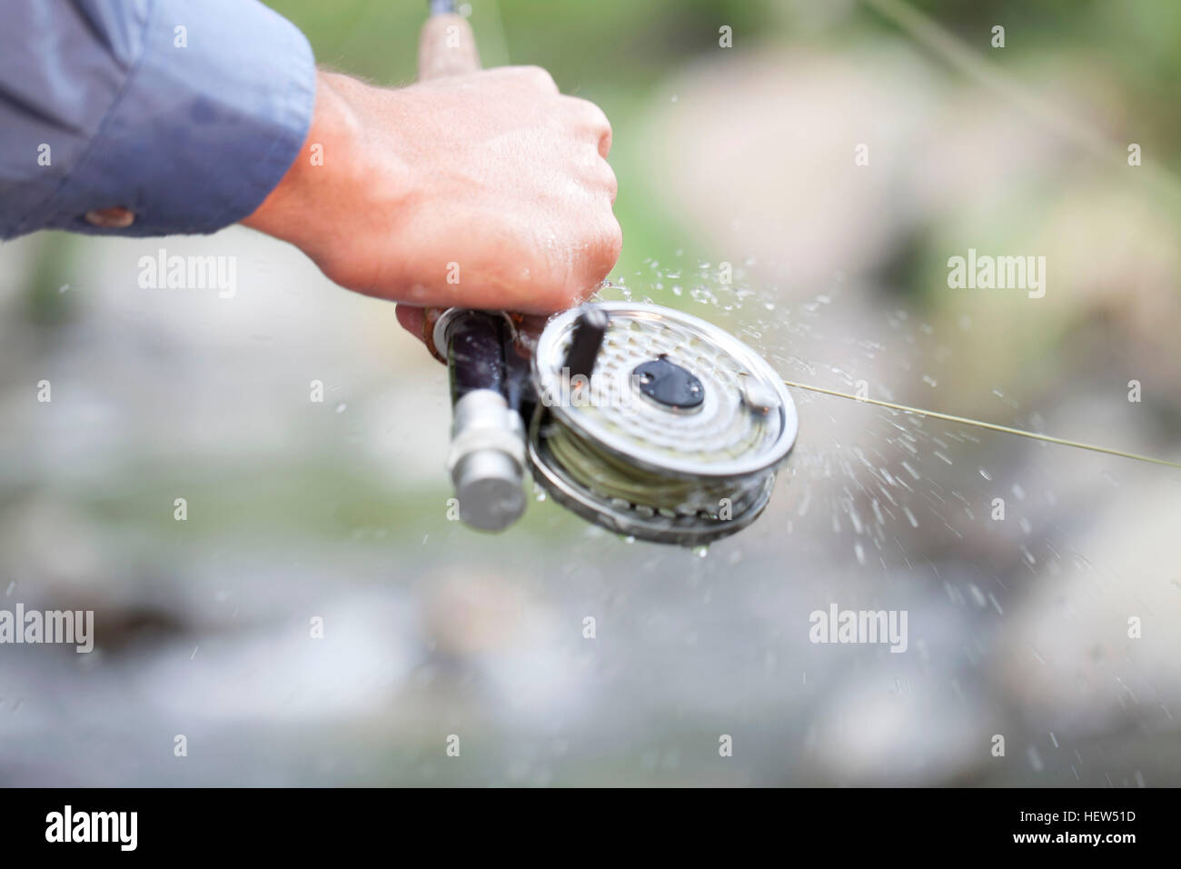 Fisherman\'s hand holding fishing rod with spinning reel Stock Photo ...