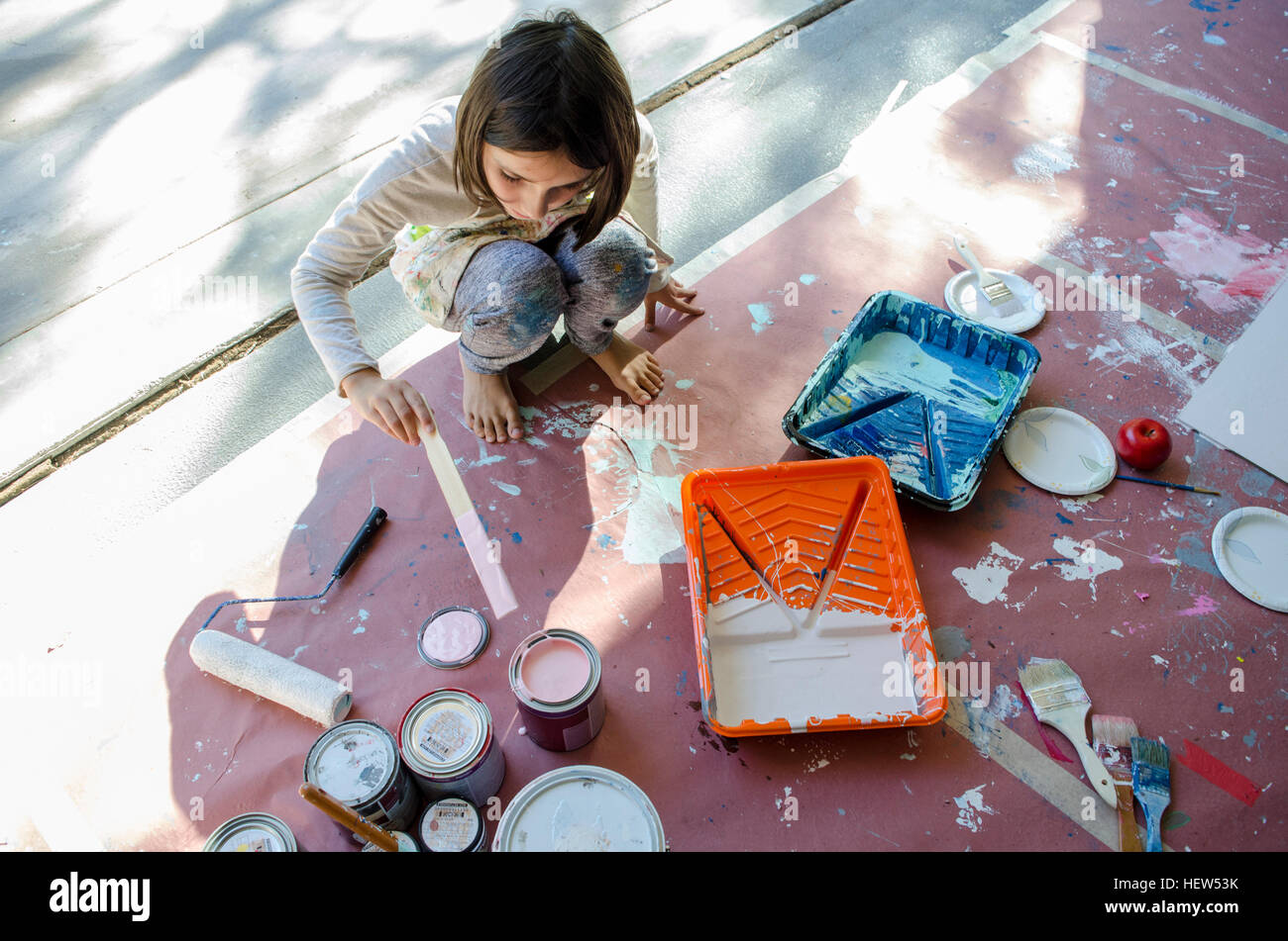 Girl in garage stirring paint in paint tins Stock Photo