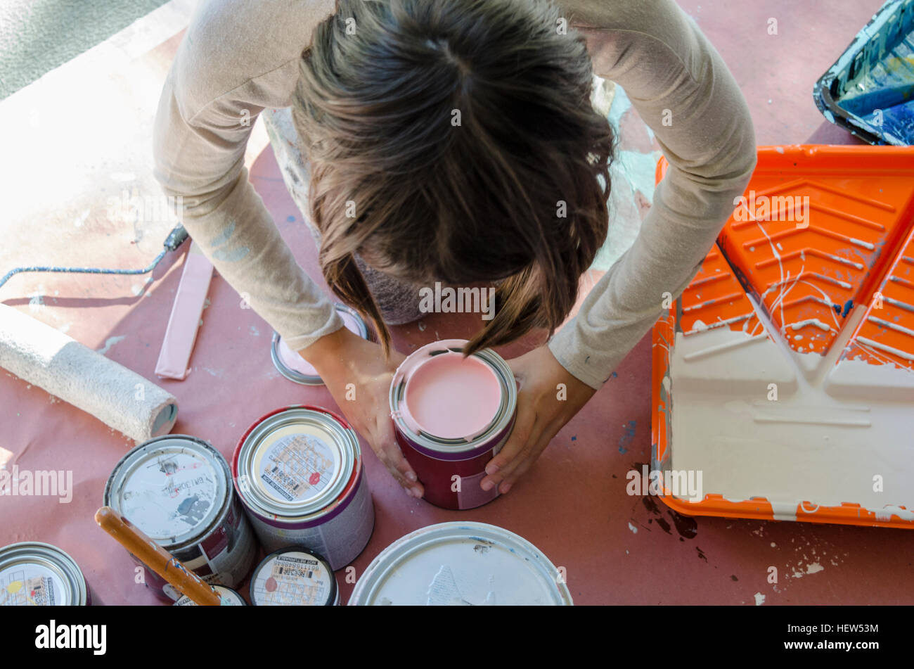 Girl in garage stirring paint in paint tins - Stock Image