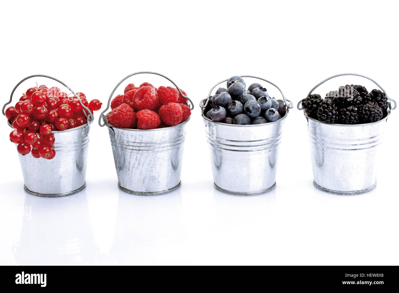 Four small galvanized buckets containing (left to right) red currants, raspberries, blueberries and blackberries - Stock Image