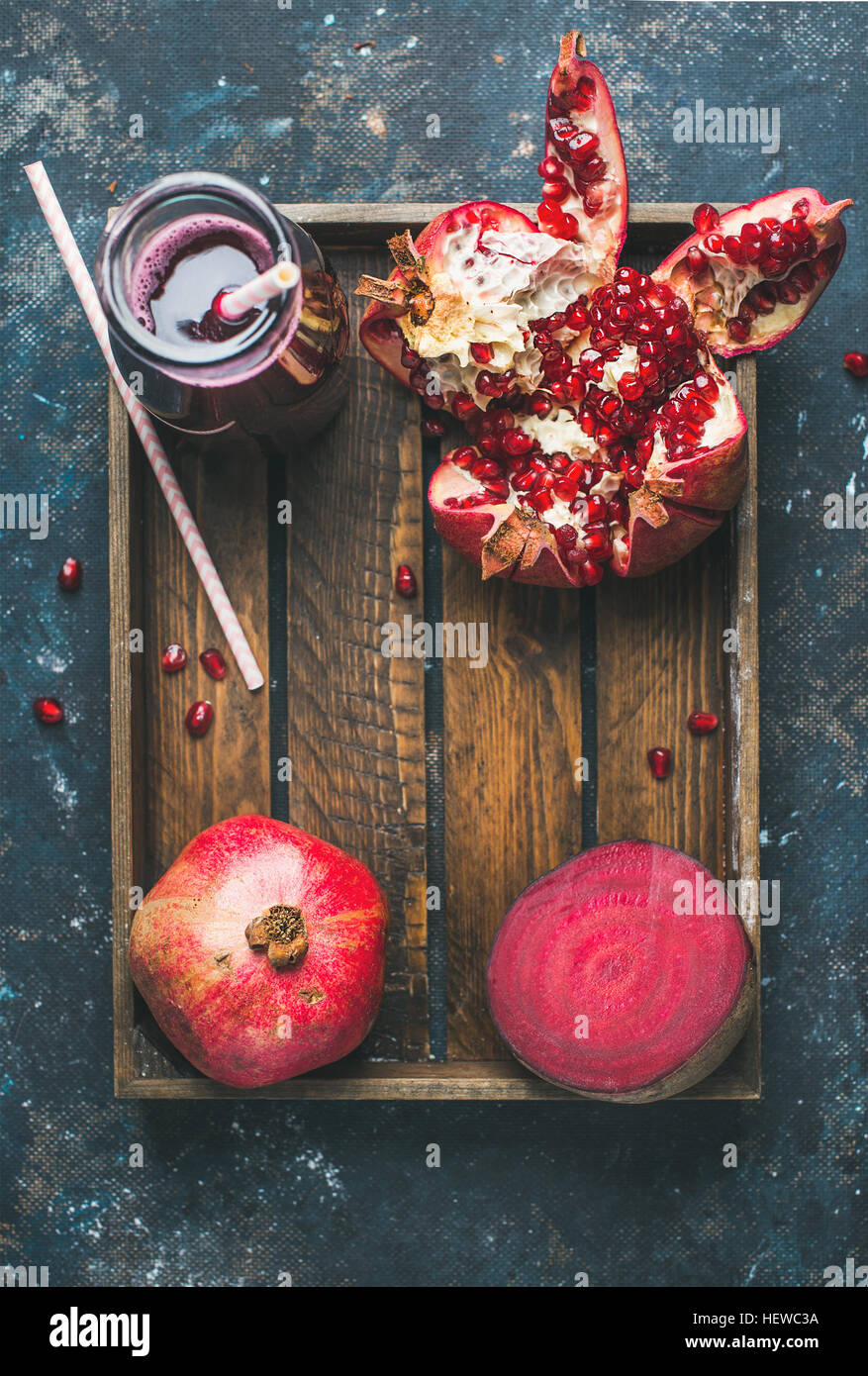 Ripe seasonal pomegranates, beetroot and freshly squeezed juice in glass - Stock Image