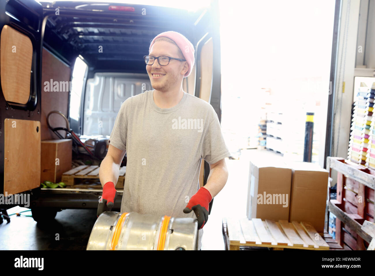 Worker in brewery, preparing to distribute barrels of beer - Stock Image
