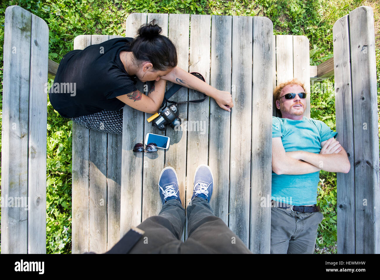Overhead point of view shot of couple resting on picnic bench - Stock Image