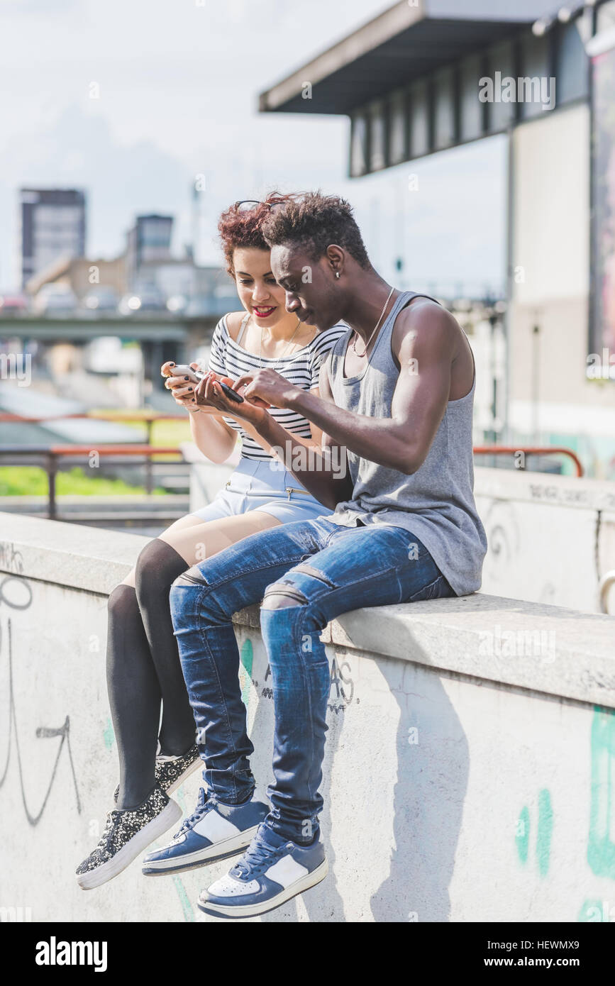 Couple in urban area looking at smartphone, Milan, Italy - Stock Image