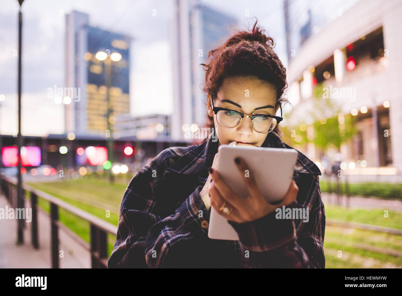 Woman in urban area using digital tablet, Milan, Italy - Stock Image