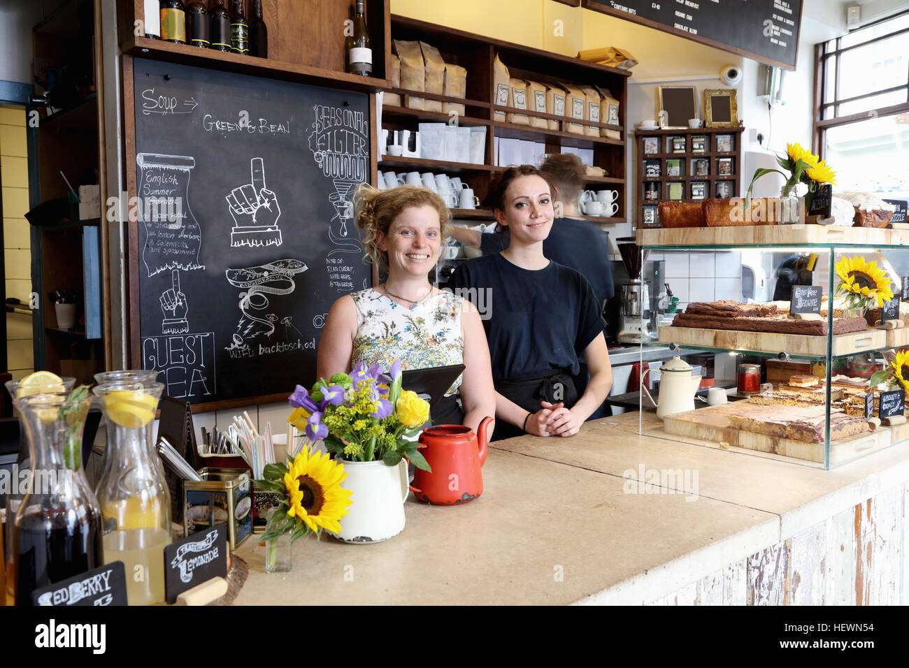 Colleagues at counter in coffee shop looking at camera smiling - Stock Image