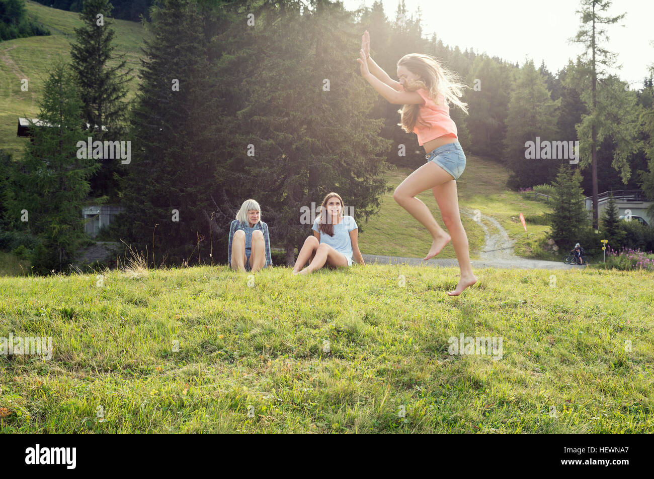 Young woman poised to cartwheel in field, Sattelbergalm, Tirol, Austria - Stock Image