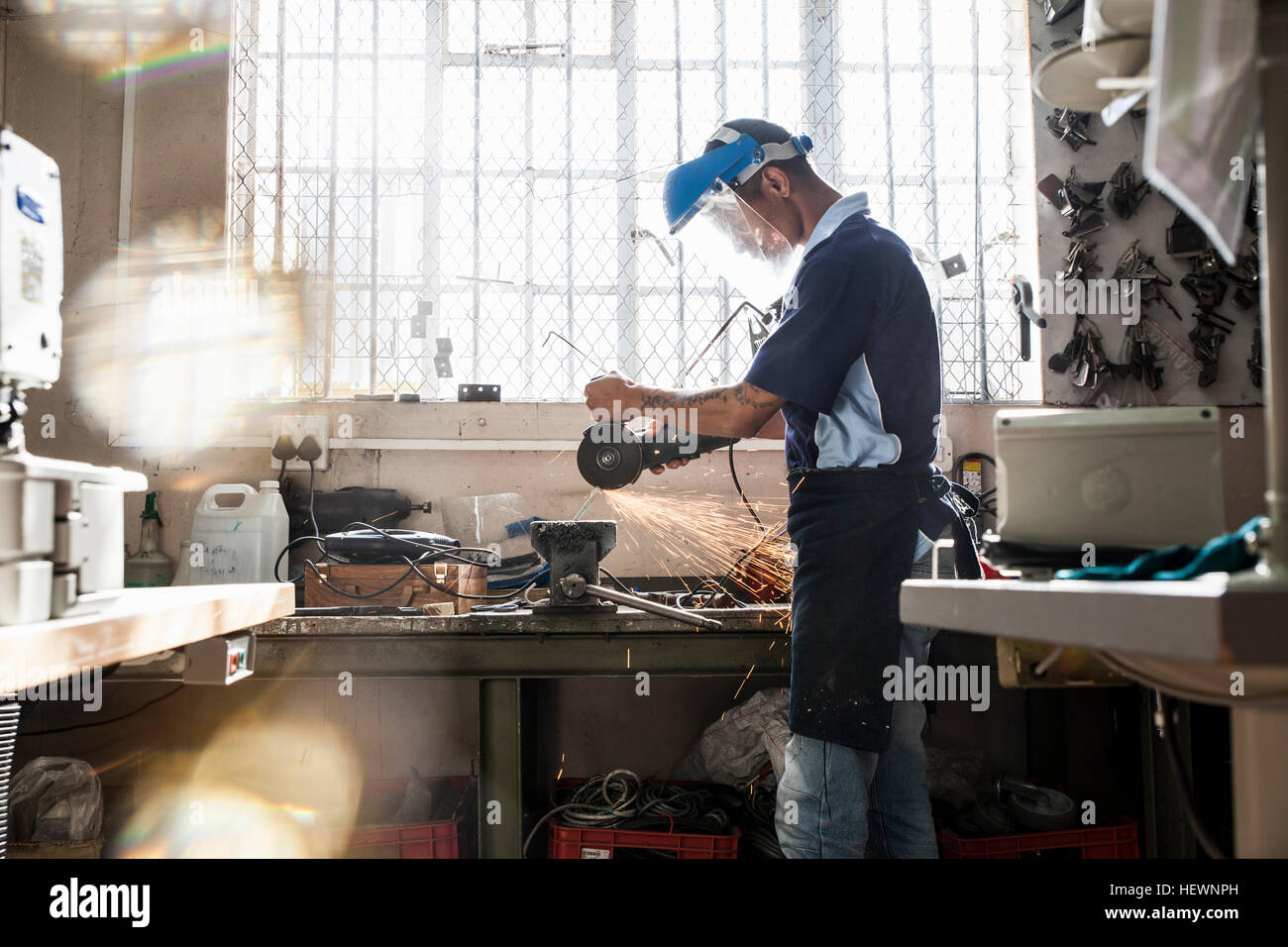 Young man using angle grinder at vice in repair workshop - Stock Image