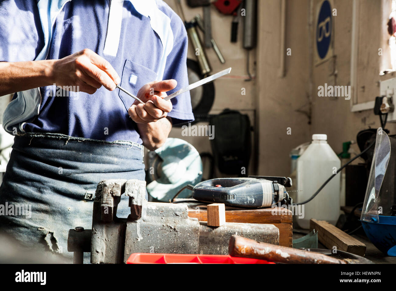 Mid section of young man using screwdriver in repair workshop - Stock Image