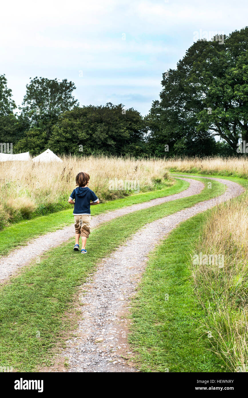 Rear view of boy walking on dirt track - Stock Image