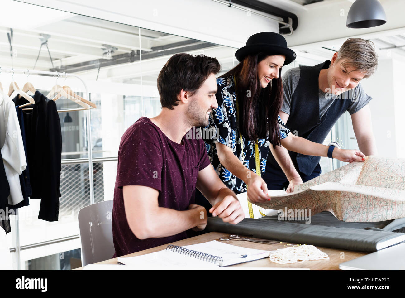 Colleagues at desk looking at folding map smiling - Stock Image
