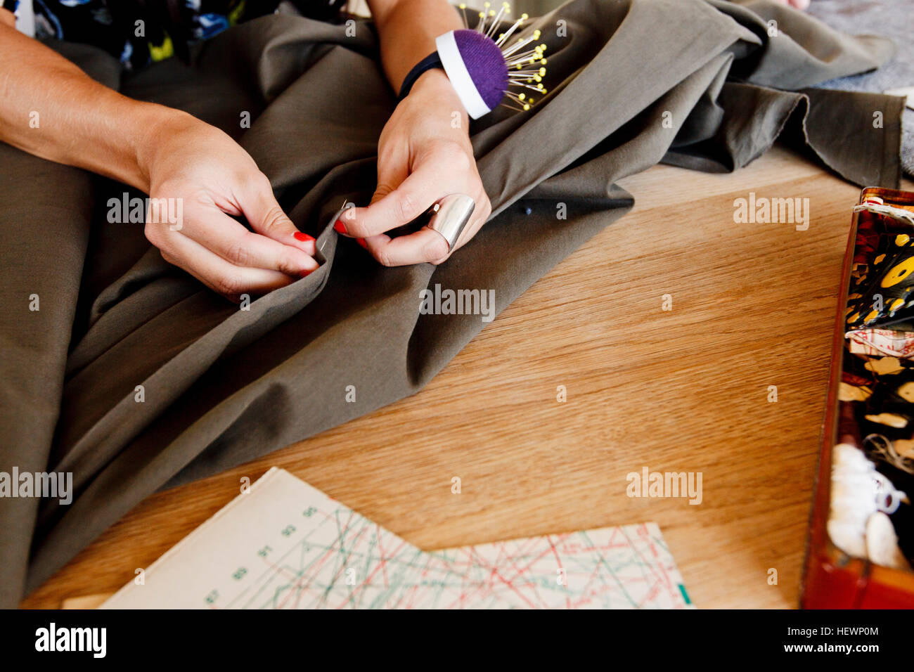 Cropped view of seamstress pinning fabric - Stock Image