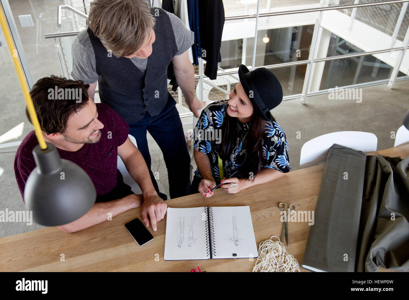 Colleagues at desk discussing fashion designs - Stock Image