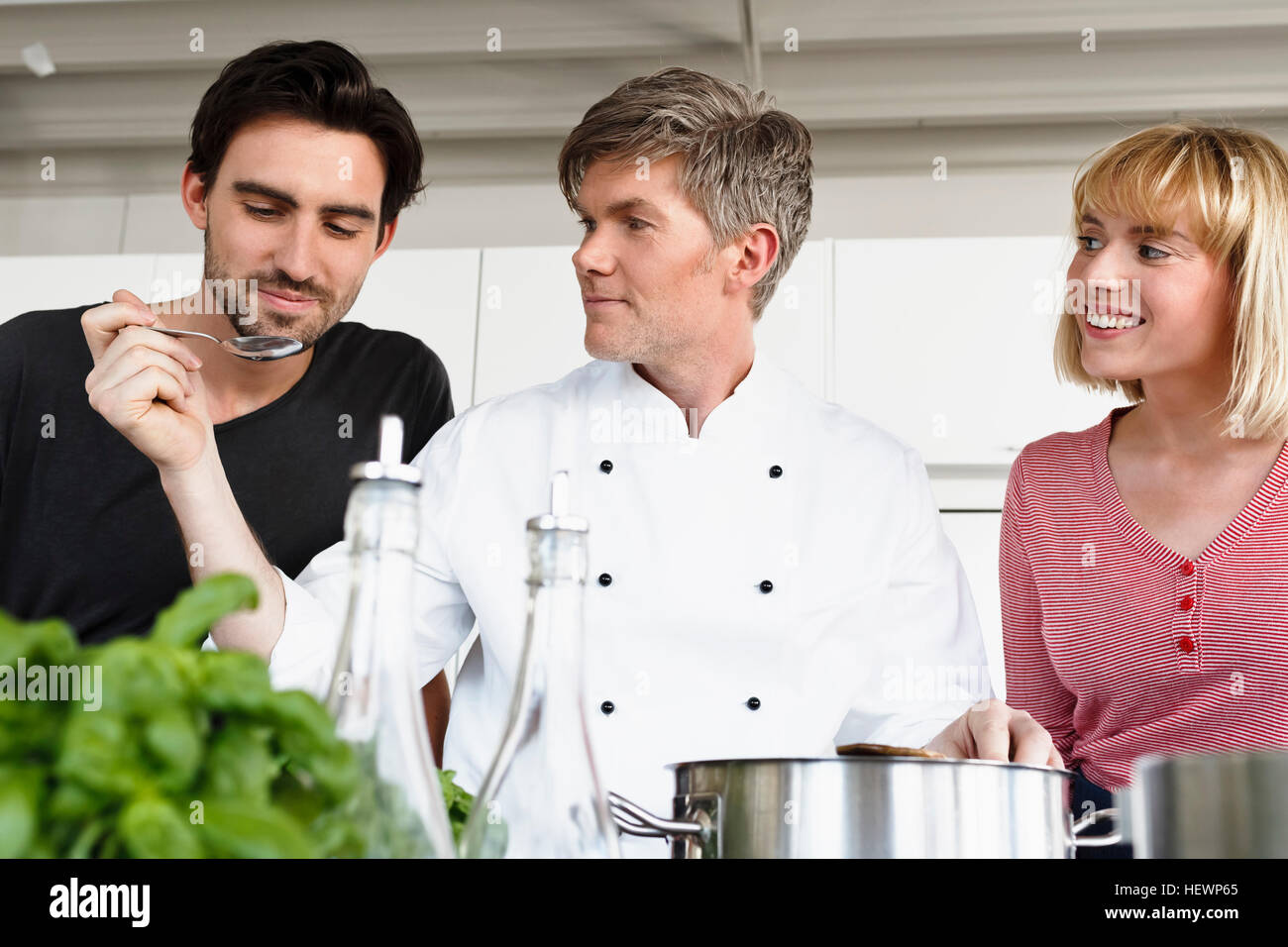 Chef and couple in kitchen tasting food Stock Photo