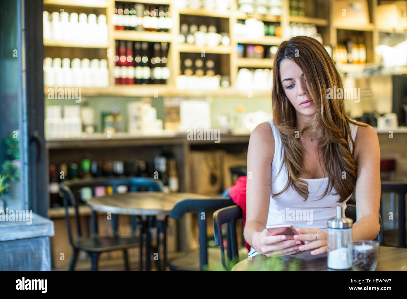 Young woman sitting in cafe reading smartphone texts - Stock Image