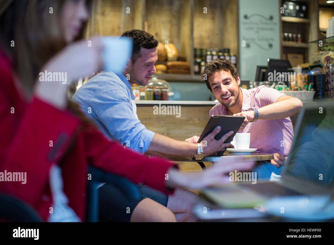 Male friends sitting in cafe pointing at digital tablet - Stock Image
