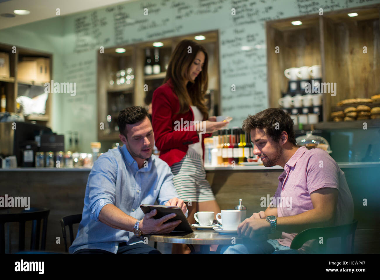 Male friends sitting in cafe looking at digital tablet - Stock Image