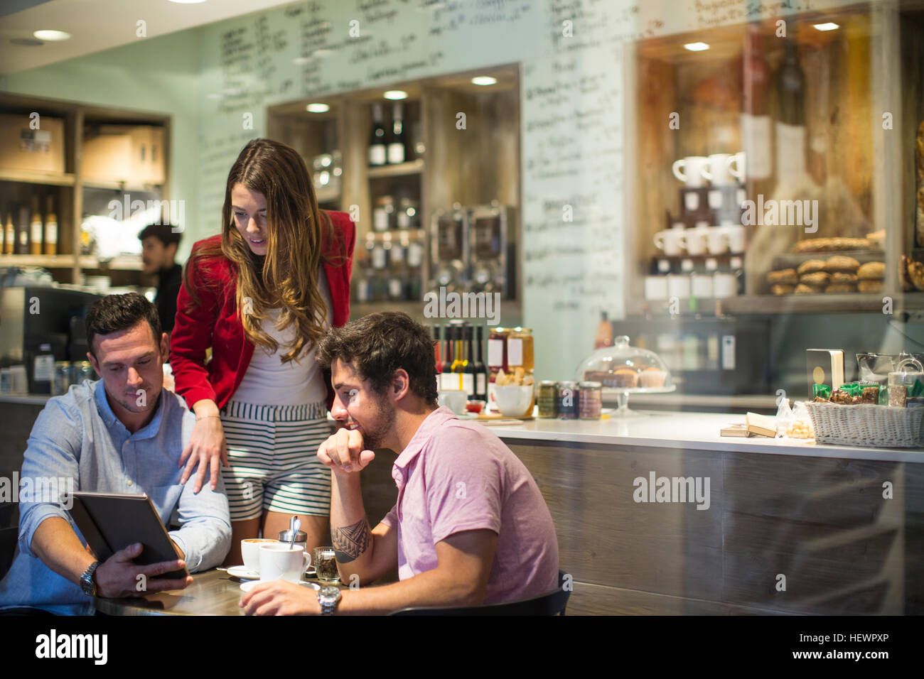Male and female friends in cafe looking at digital tablet - Stock Image