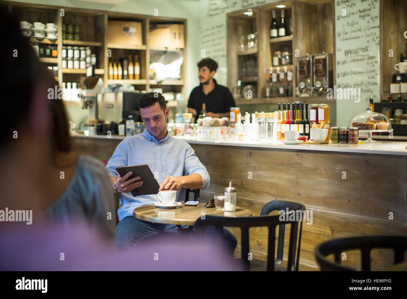 Man sitting in cafe browsing digital tablet - Stock Image