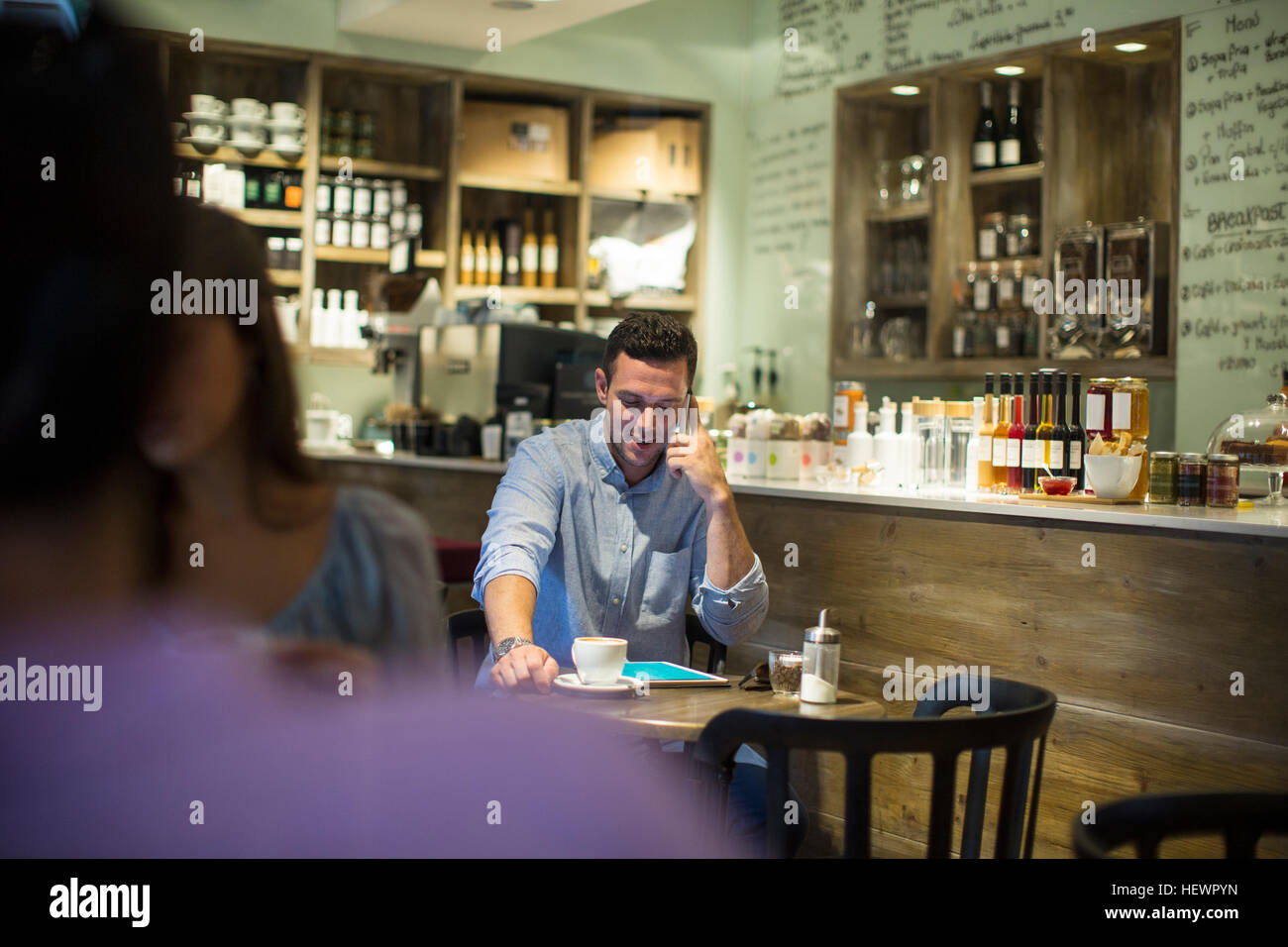 Man sitting in cafe talking on smartphone - Stock Image