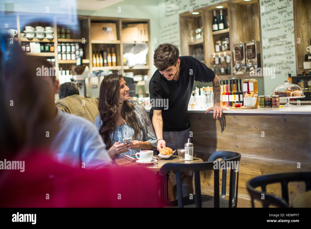 Barista serving young female customer in cafe - Stock Image
