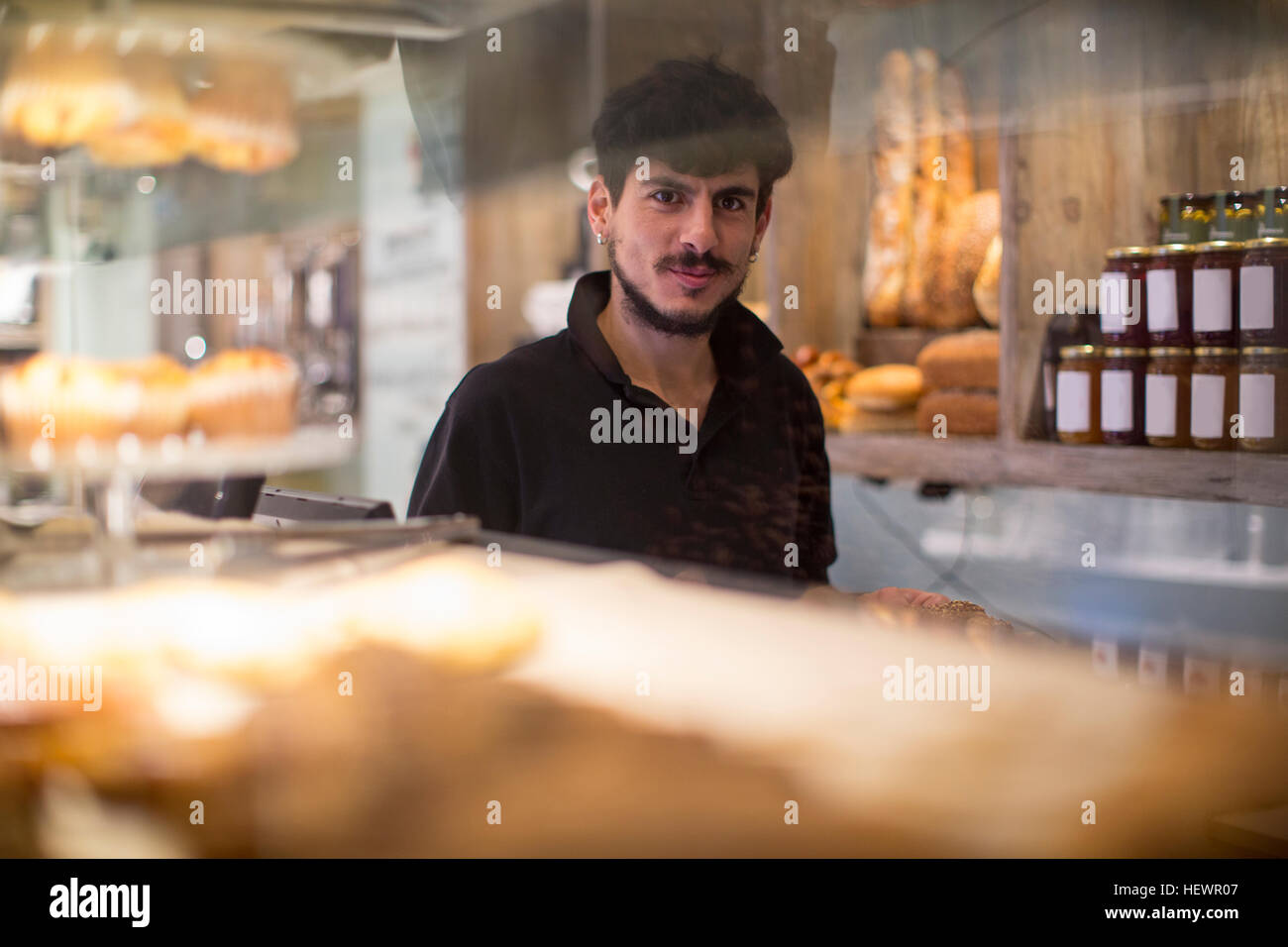 Portrait of young male barista behind cafe counter - Stock Image
