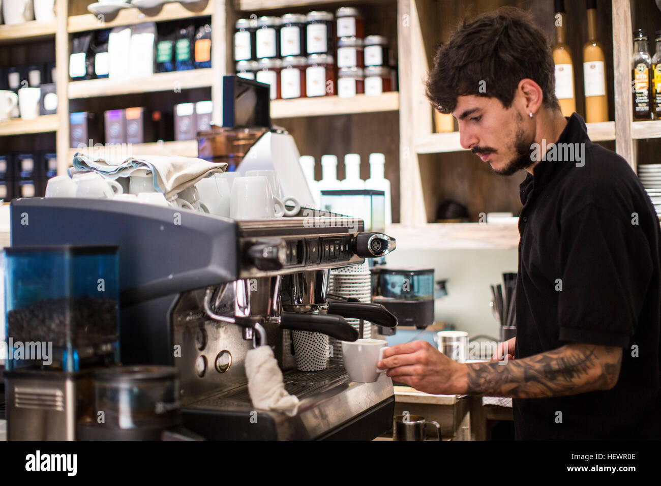 Young male barista using coffee machine in cafe - Stock Image