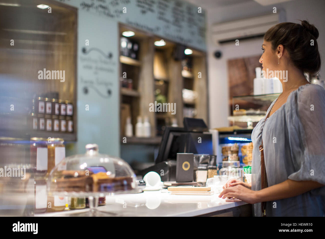 Young woman waiting at cafe counter - Stock Image