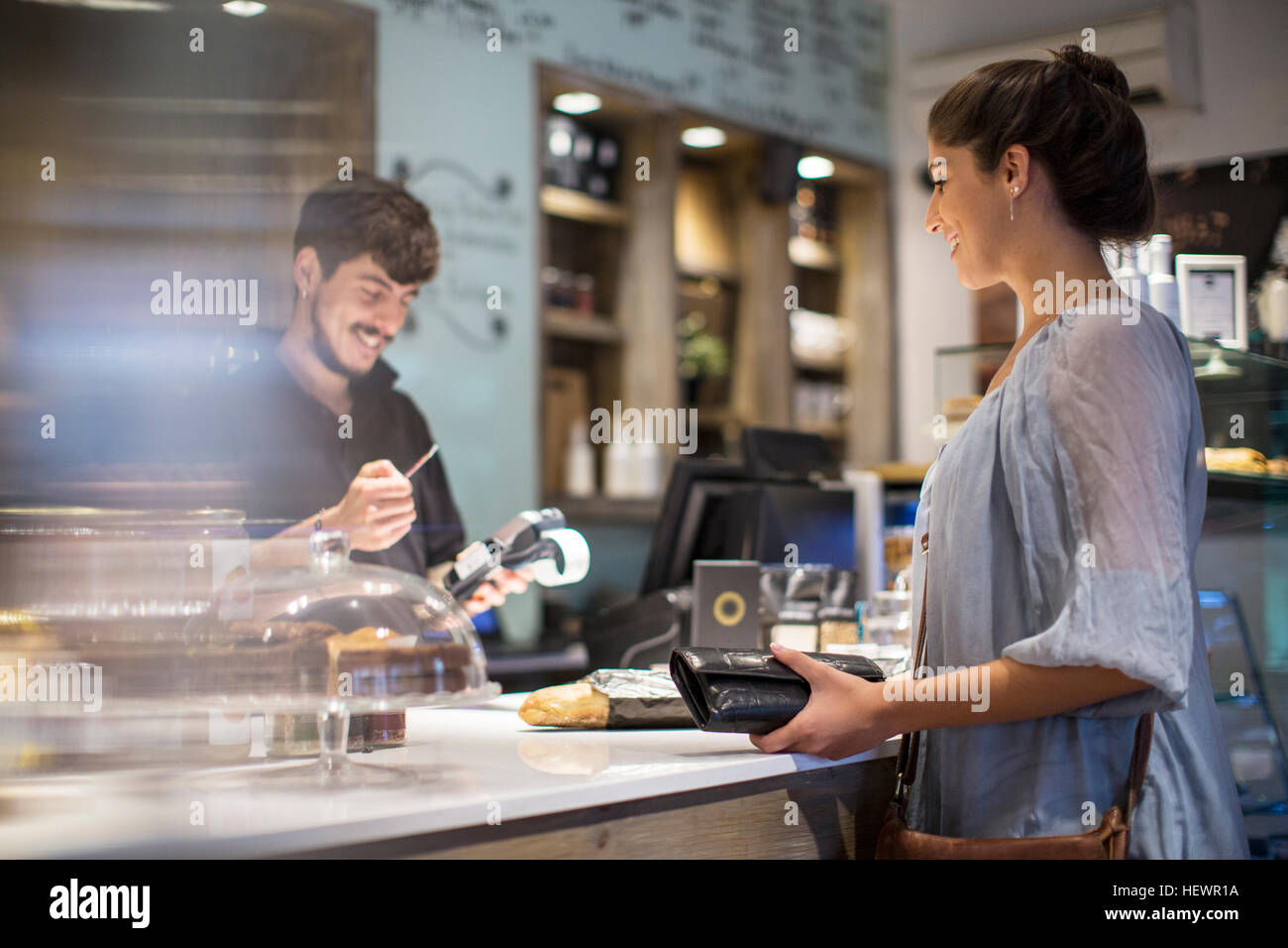 Barista calculating bill for female customer at cafe counter - Stock Image