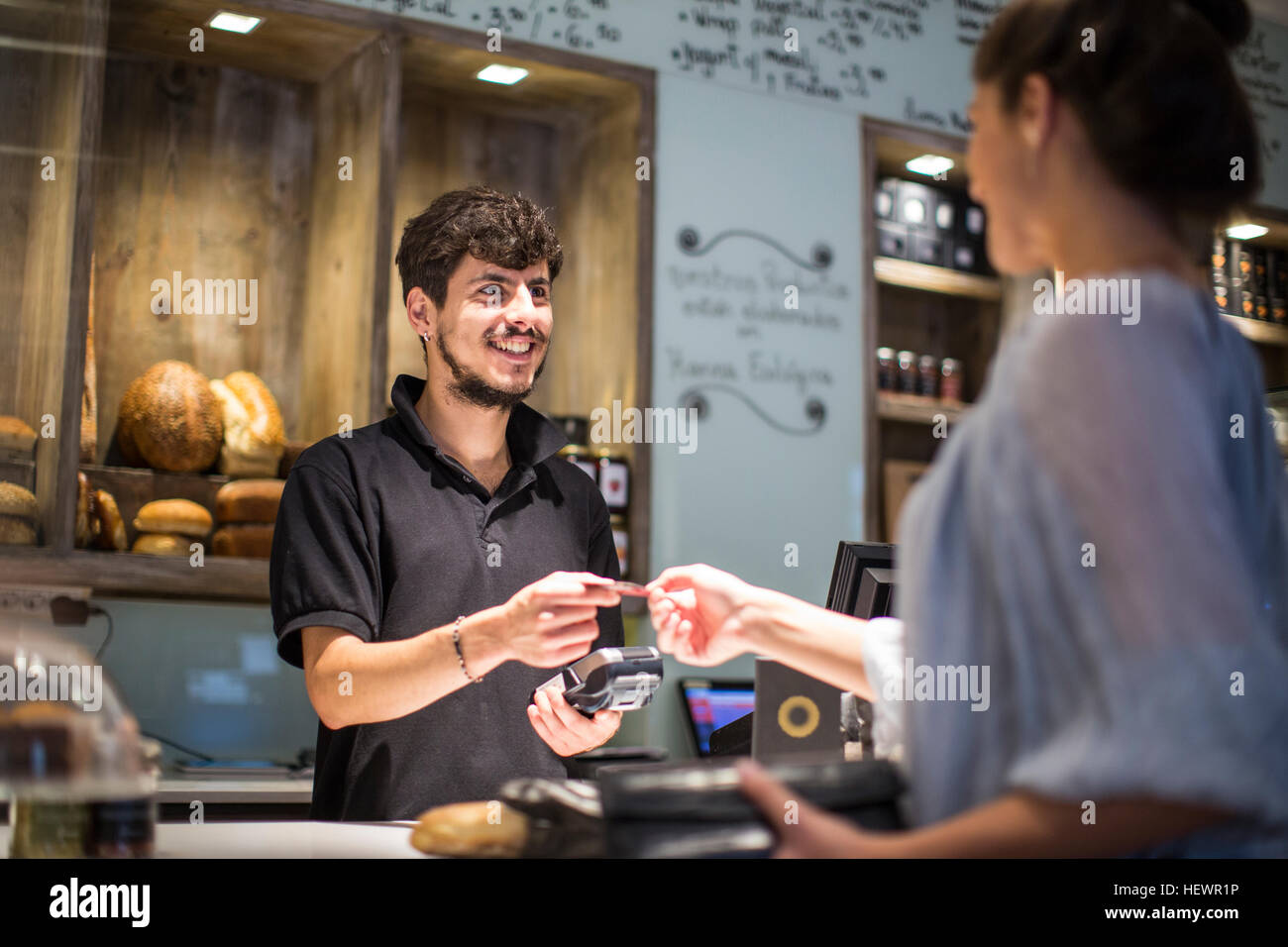 Barista handing credit card to female customer at cafe counter - Stock Image