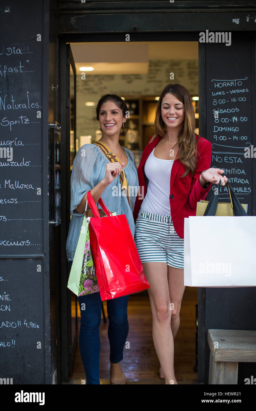 Two young female friends leaving cafe carrying shopping bags Stock Photo