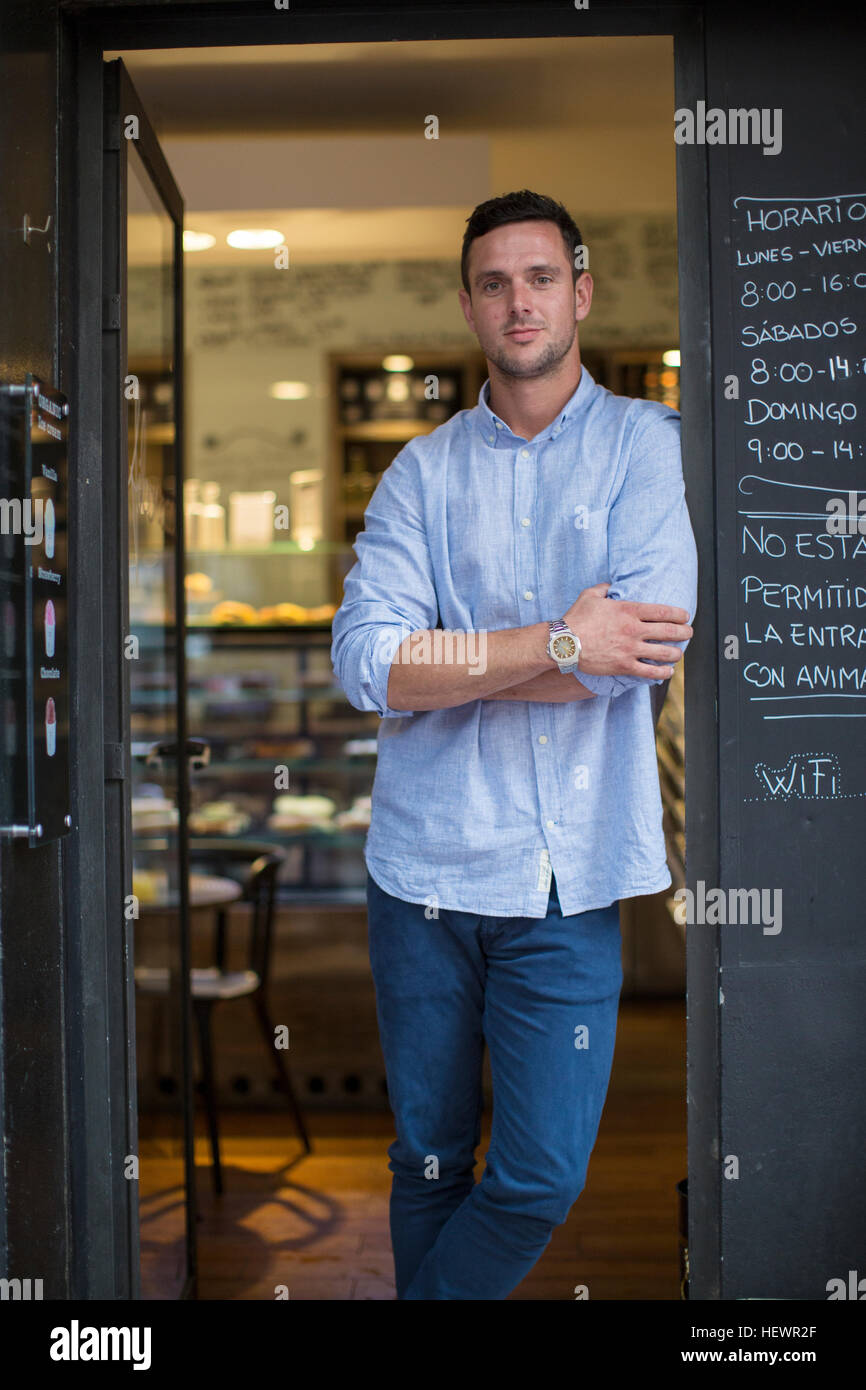 Portrait of mid adult male cafe owner leaning against cafe doorway - Stock Image