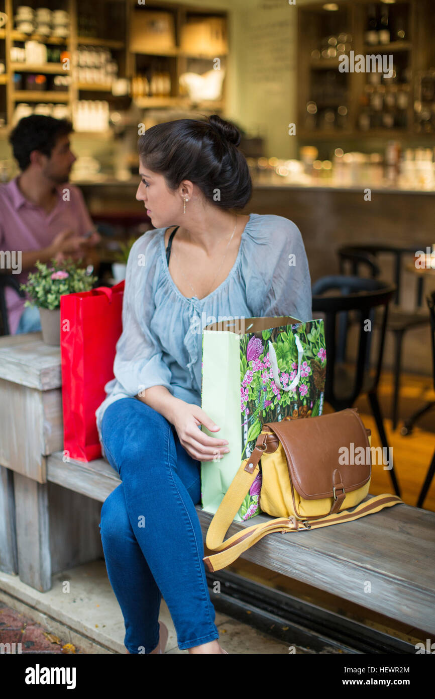 Young woman shopper sitting outside cafe looking over her shoulder Stock Photo