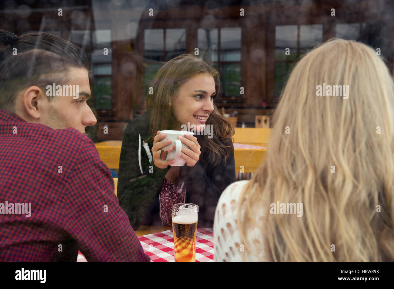 Three young adult friends with herbal tea and beer in cafe - Stock Image