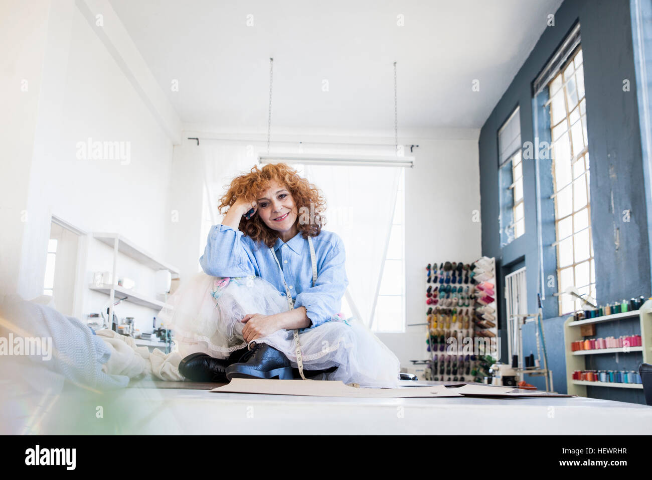 Fashion designer sitting cross-legged on desk looking at camera smiling - Stock Image