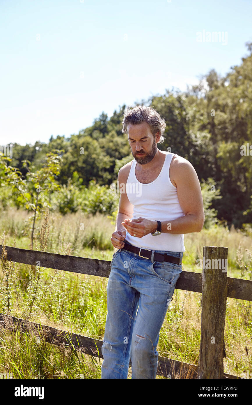 Mid adult man leaning against rural fence gazing at blade of grass - Stock Image