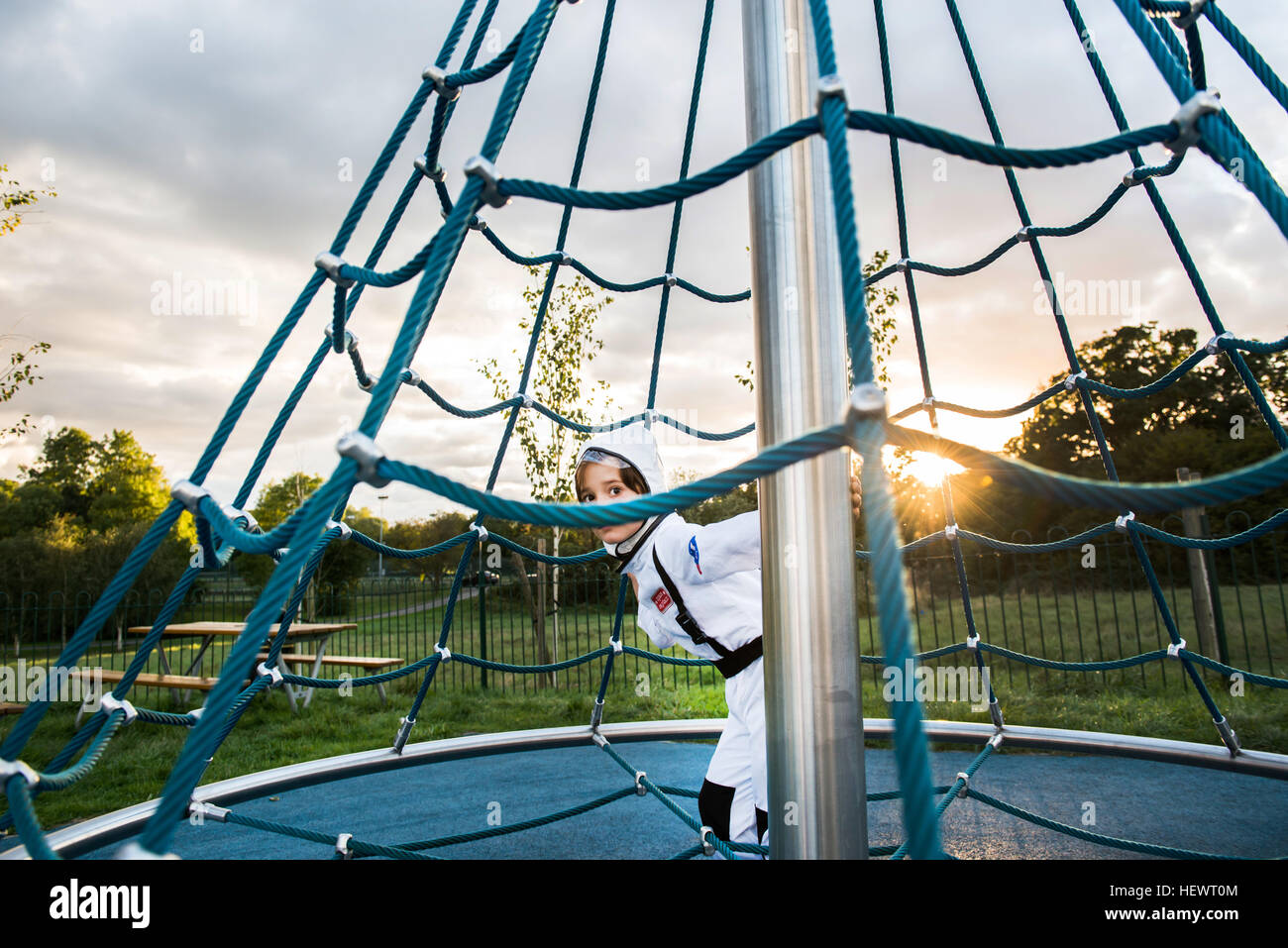 Portrait of boy in astronaut costume hiding and peering from playground climbing frame - Stock Image