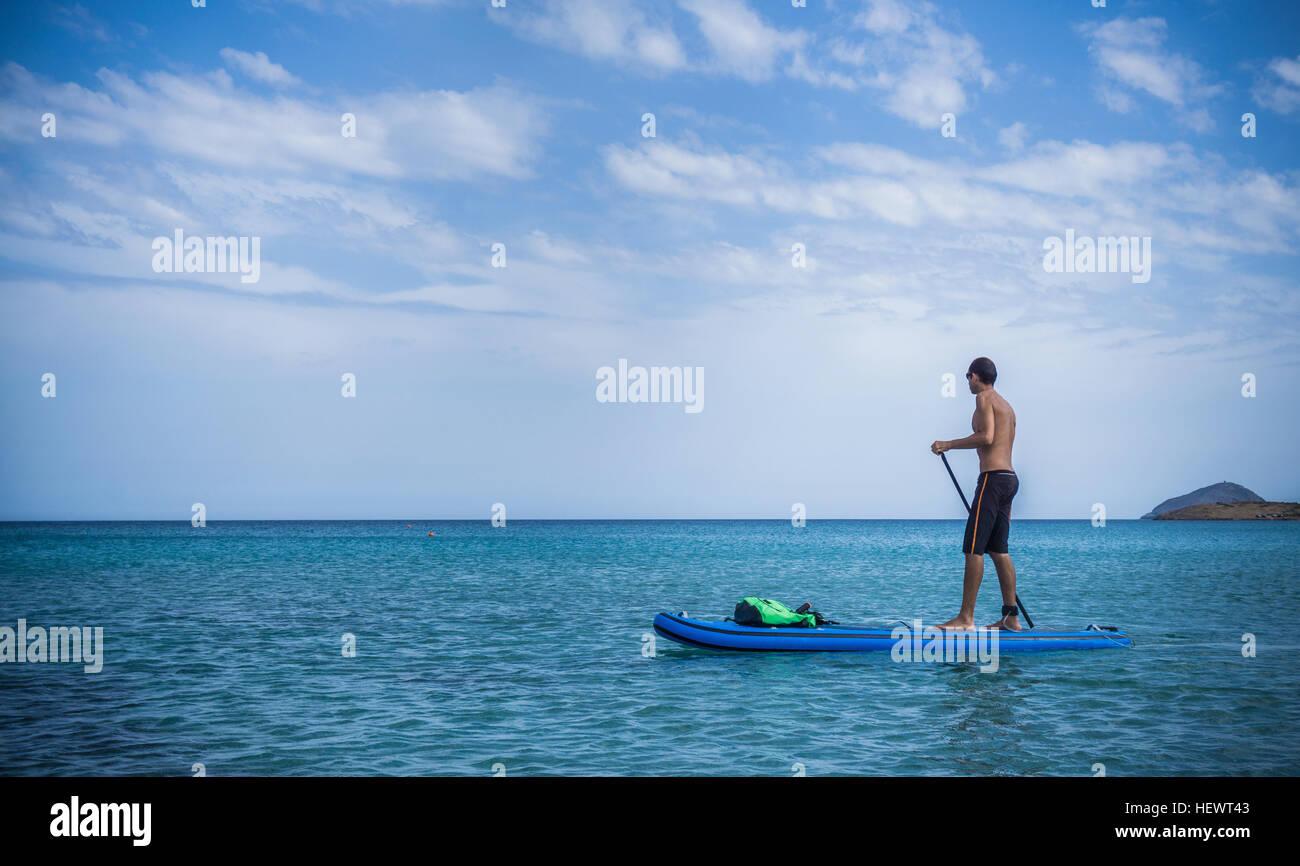 Man paddleboarding, Olbia, Sardinia, Italy - Stock Image