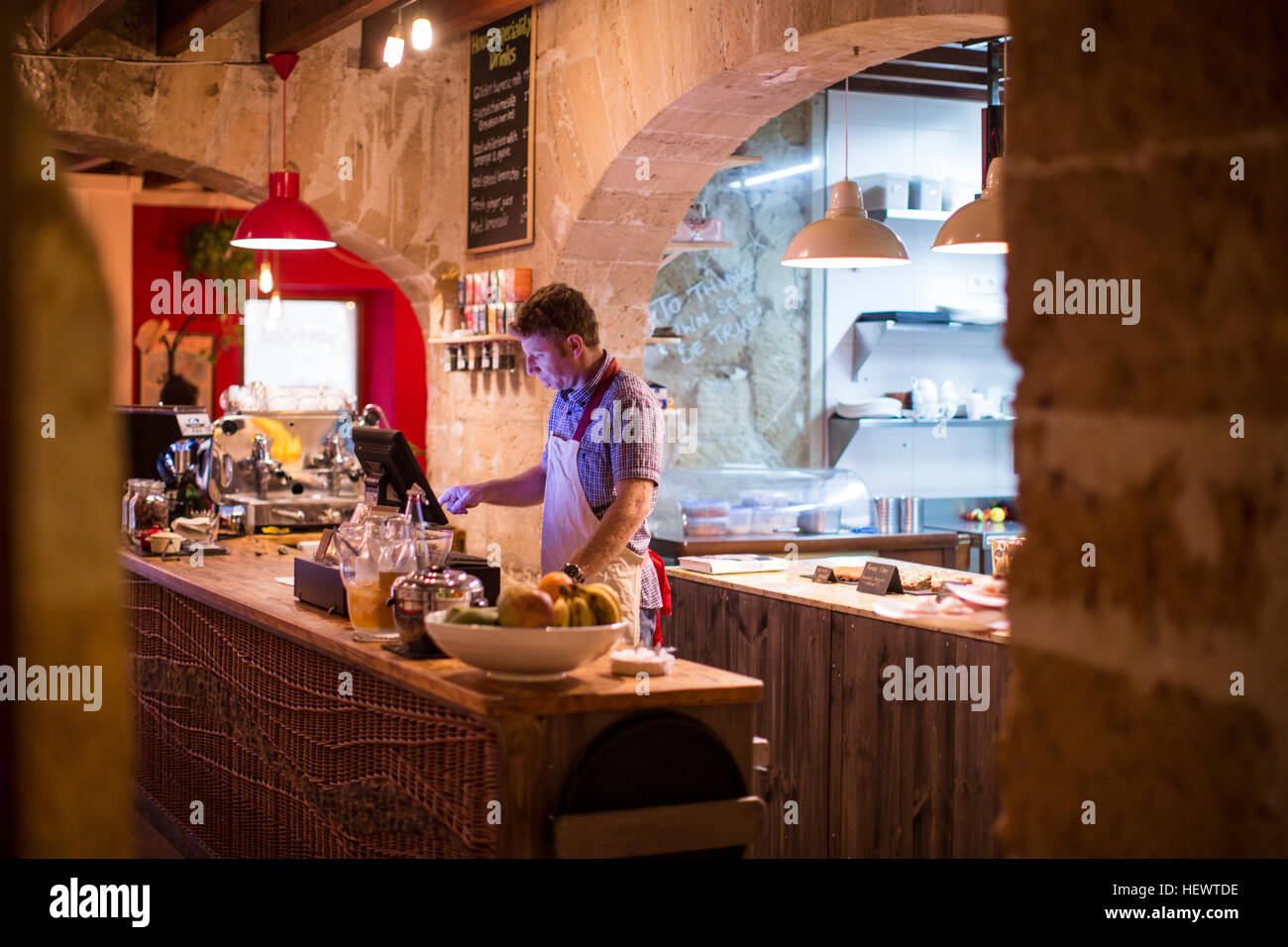 Restaurant owner working behind cash register - Stock Image