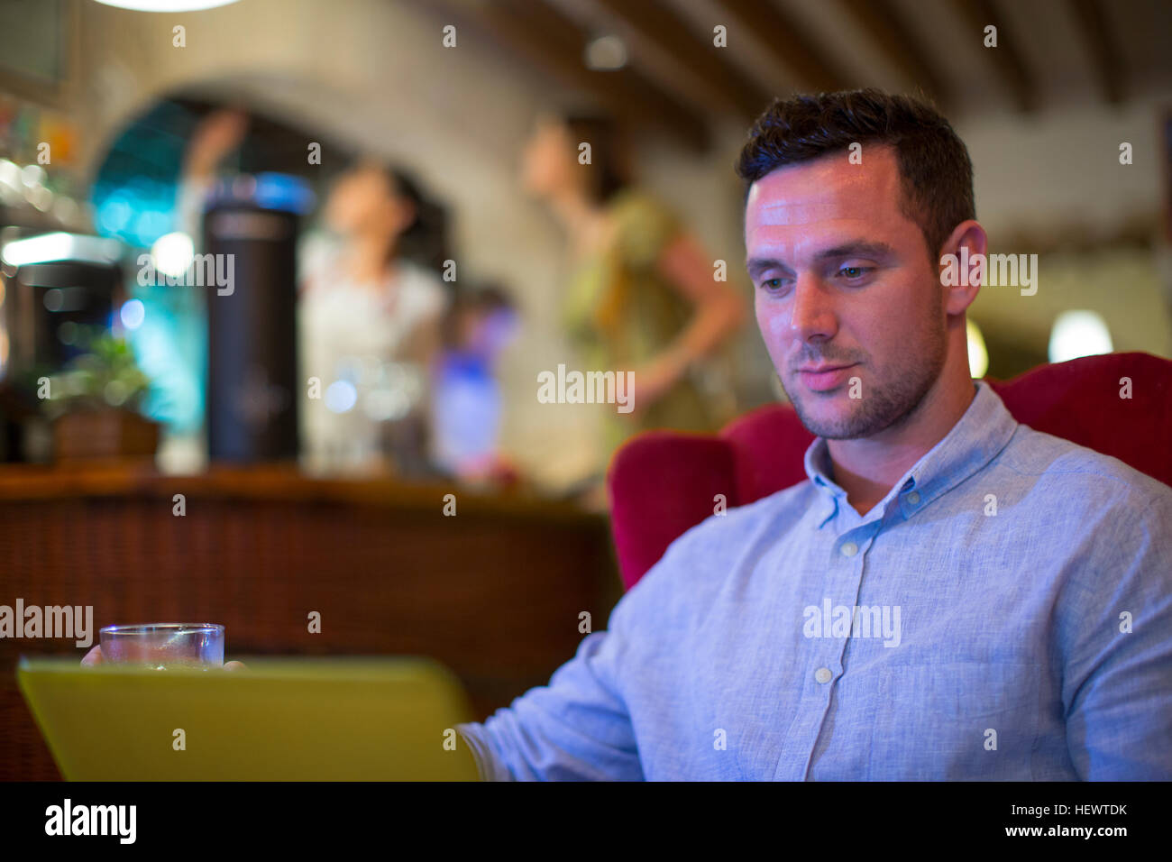 Man using laptop in restaurant - Stock Image