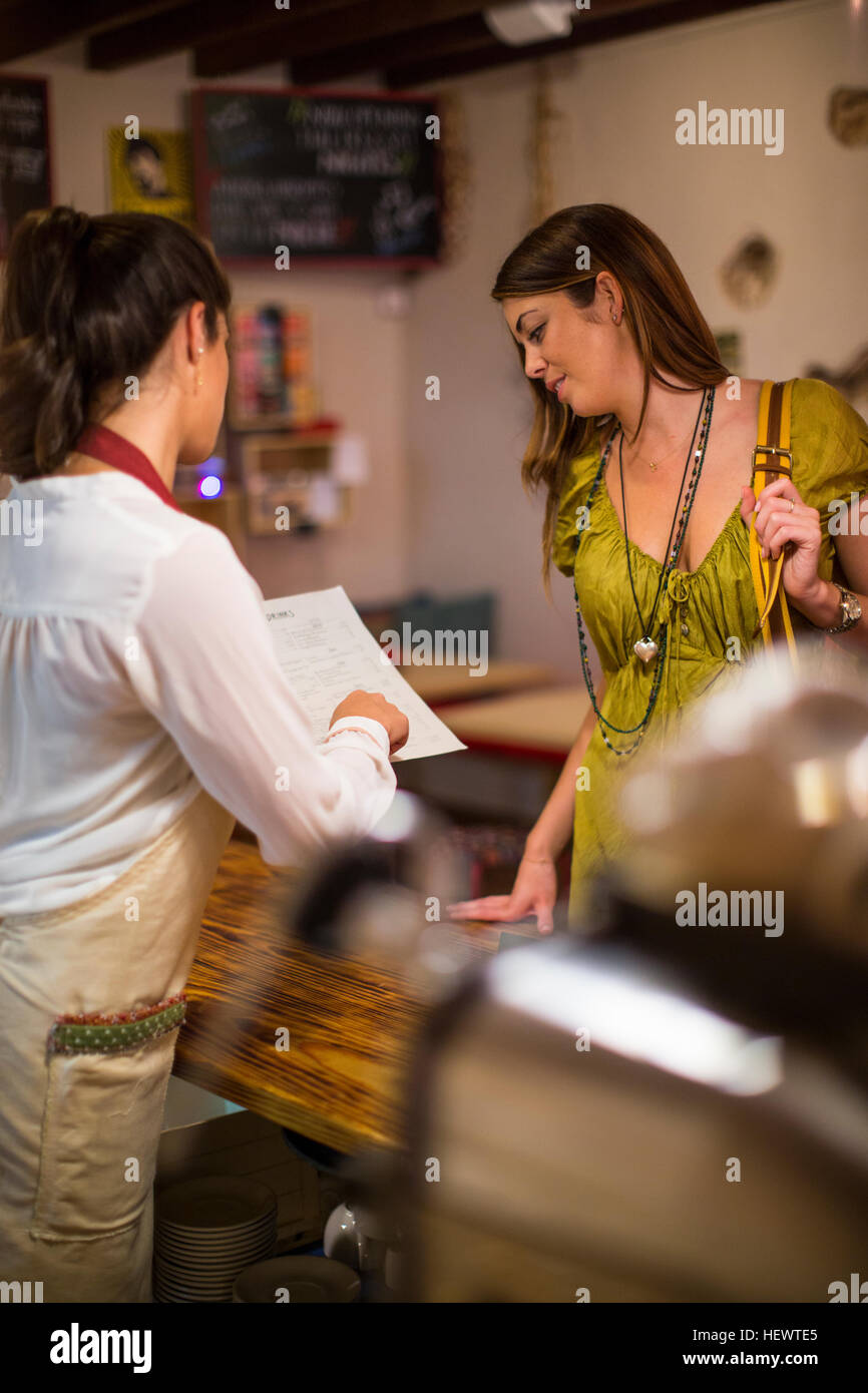 Restaurant owner serving customer in cafe - Stock Image