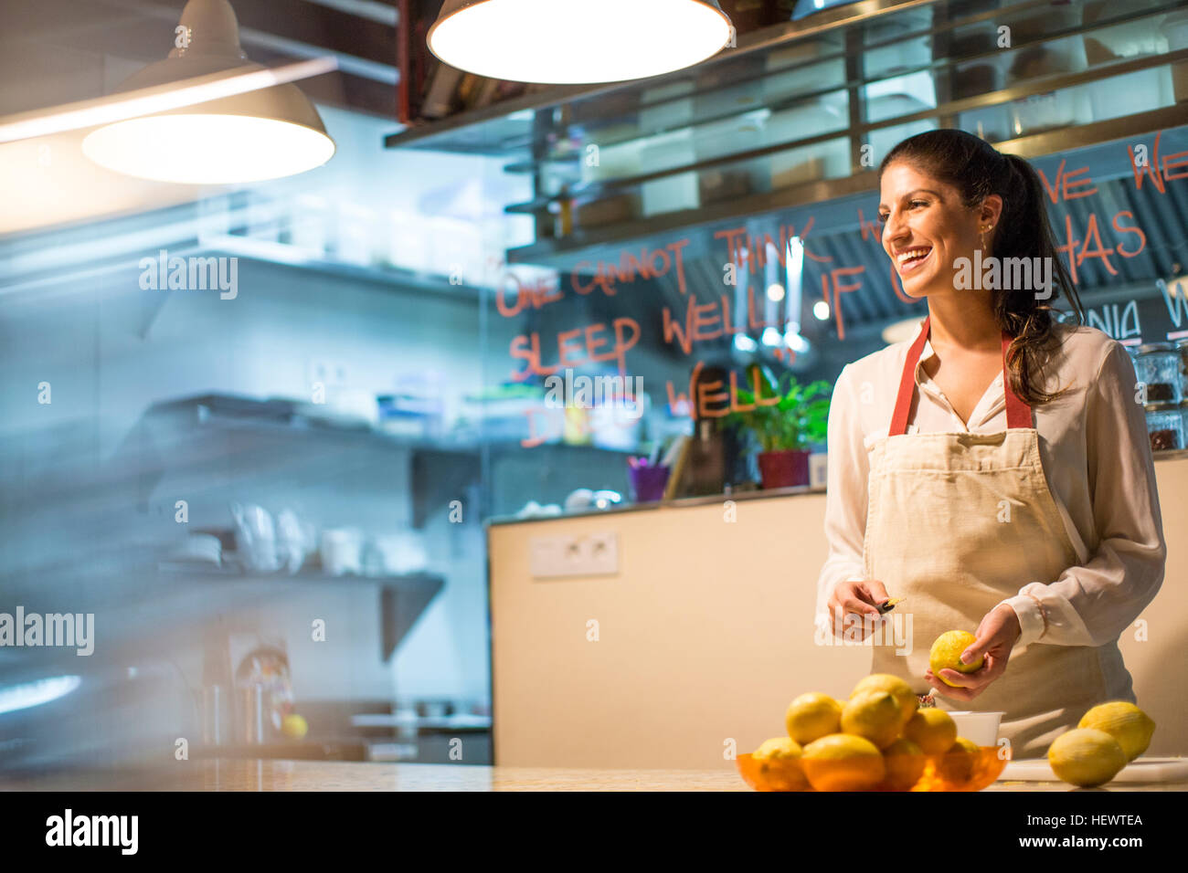 Restaurant owner peeling lemons in kitchen - Stock Image