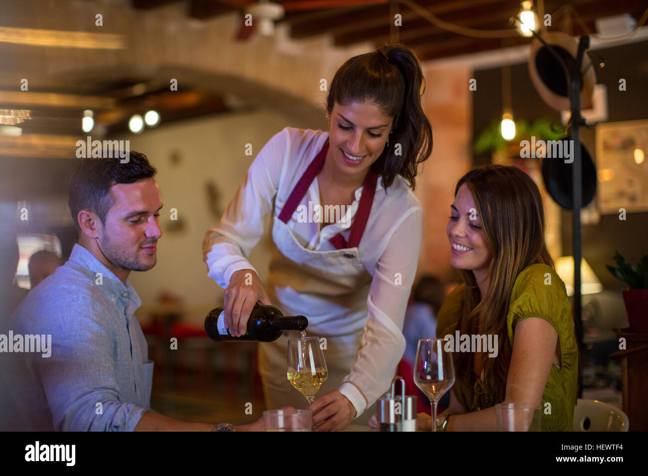 Waitress serving wine to customers in restaurant - Stock Image