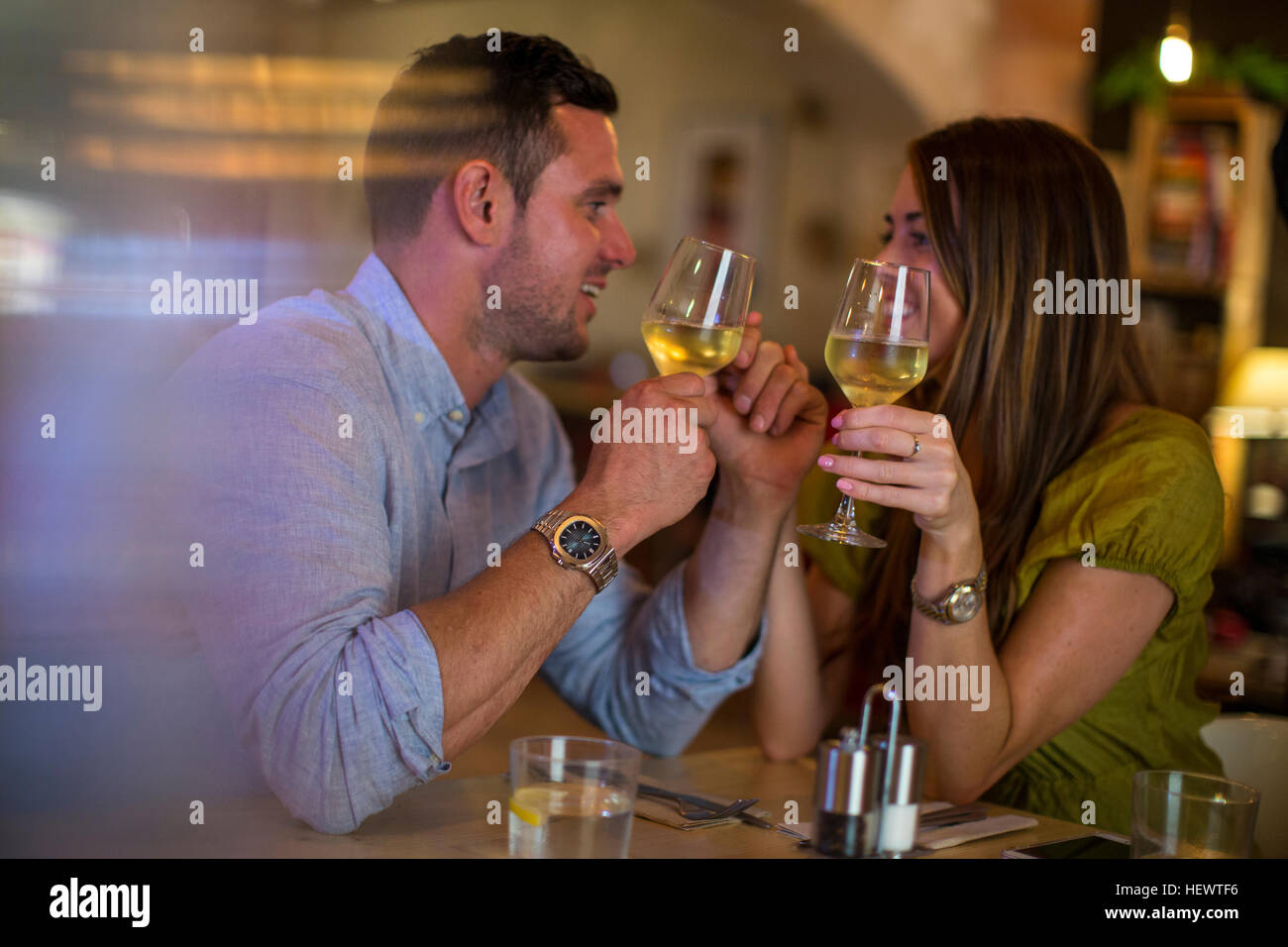 Couple toasting wine in restaurant - Stock Image