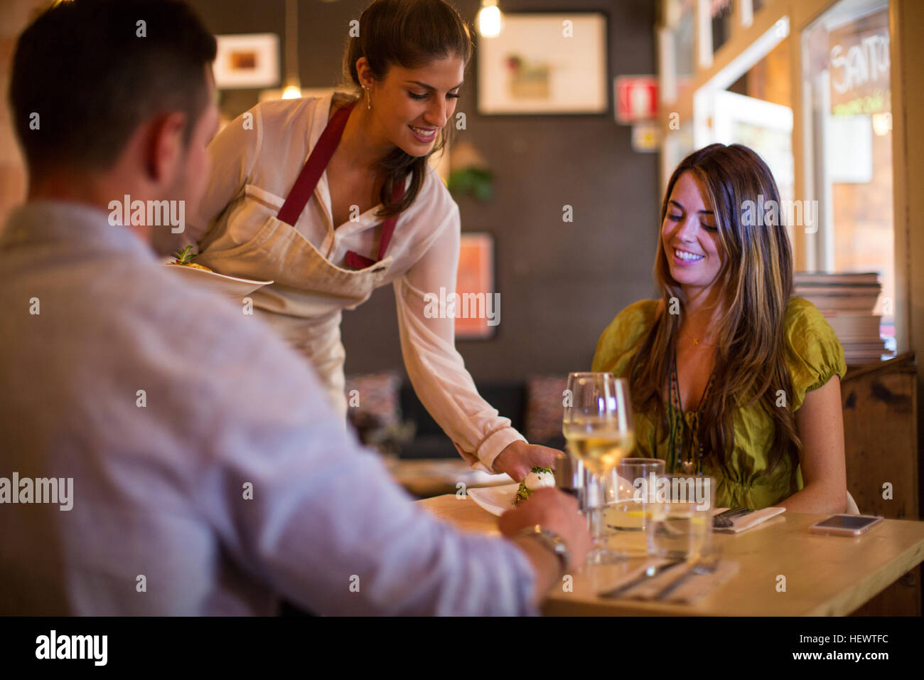 Waitress serving customers in restaurant - Stock Image